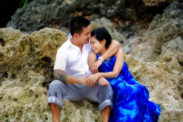 Bunn Salarzon - guy hugs girl sitting on rock at beach