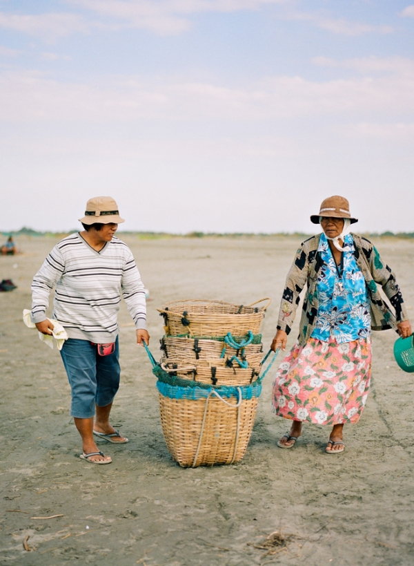 Bunn Salarzon - two old women carrying basket of fish on the beach