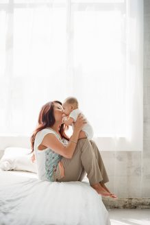 Asian mom sitting on white bed kissing baby boy